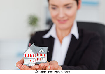 Smiling businesswoman holding a miniature house