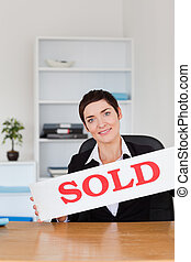 Portrait of a real estate agent with a sold panel in her...