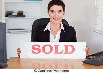 Cute real estate agent with a sold panel