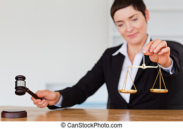 Serious judge with a gavel and the justice scale in her...
