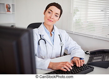 Cute doctor looking at her computer in her office