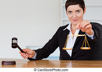 Judge with a gavel and the justice scale in her office
