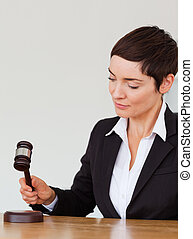 Portrait of a woman knocking a gavel