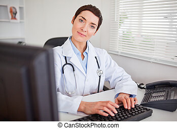 Cute female doctor typing with her computer in her office