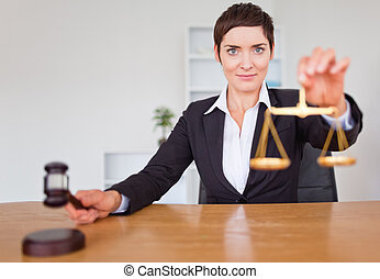 Serious woman with a gavel and the justice scale in her...