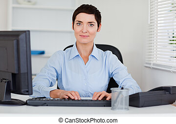 Portrait of a businesswoman typing with her computer while...