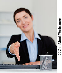 Portrait of a young business woman giving her hand with the...
