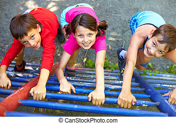 Up - Three little children climbing ladder and looking at...