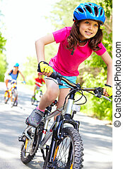 The fastest cyclist - A cute girl riding her bicycle with...