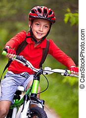 Athletic child  - Portrait of a boy riding a bike