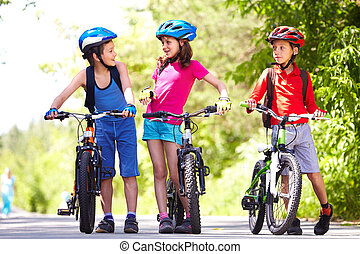 Riding bikes together - Portrait of three little children...