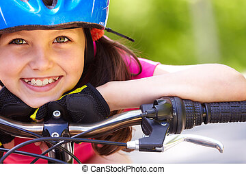 Cute athlete - Close-up of a little girls face on bike...