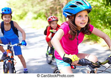 Bicycle race - A little girl riding her bike with two...