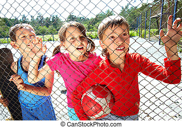 Behind the netting - Three children at playground standing...