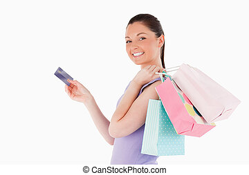 Attractive woman with a credit card holding shopping bags...