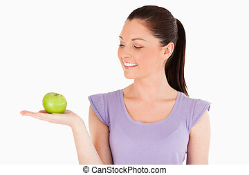Good looking woman holding an apple while standing against a...