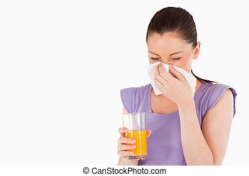 Good looking woman holding a glass of orange juice and...