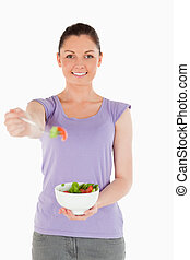 Attractive woman holding a bowl of salad while standing