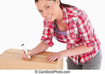 Portrait of an attractive woman writing on cardboard boxes...