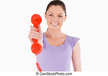 Good looking woman holding a red telephone while standing...