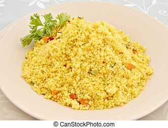 couscous dish with parsley leaf decorated with several...