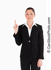 Attractive woman in suit pointing at a copy space