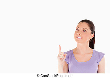 Cute woman pointing at a copy space