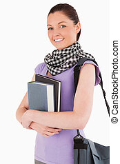 Charming student holding books and her bag while standing...