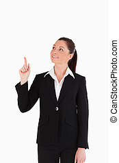 Beautiful female in suit pointing at a copy space