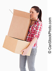 Beautiful woman looking inside a cardboard box while standing