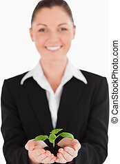 Charming woman in suit holding a small plant