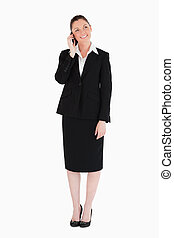 Beautiful woman in suit on the phone while standing against...