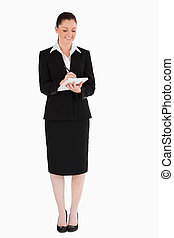 Beautiful woman in suit writing on a notebook