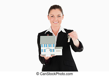 Good looking woman in suit holding keys and a miniature...