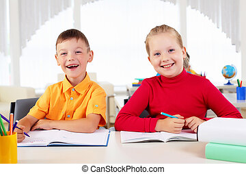 Boy and girl sitting together at a desk at school.