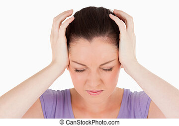 Portrait of an attractive woman having a headache while standing against a white background