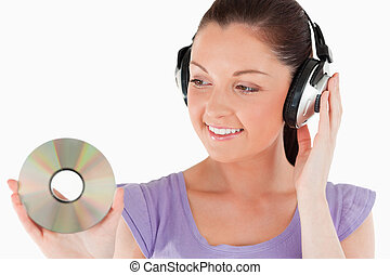 Beautiful woman with headphones holding a CD while standing...