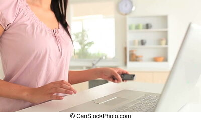 Woman answering to her phone while using her laptop in her...
