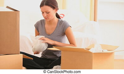 Woman preparing boxes to move out while sitting on the floor
