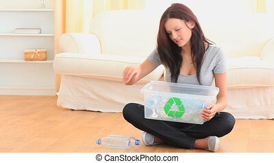 Woman sorting her waste in he living room