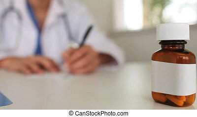 Female doctor writing a prescription with the camera focus...