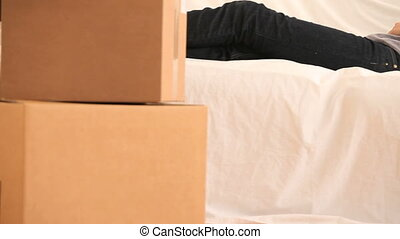Young woman resting surrounded by boxes