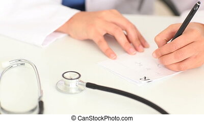Feminine hands writing a prescription on a table