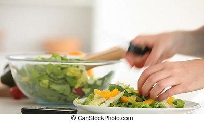 Feminine hands preparing a salad in a kitchen