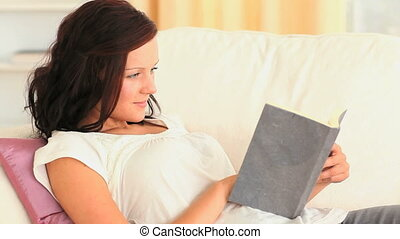 Smiling brunette reading a book in her living room