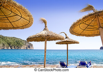 Andratx Port de Mar beach with sunroof umbrellas in blue...