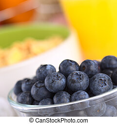Fresh blueberries in glass bowl with a bowl of cereal and orange juice in the back (Selective Focus, Focus on the middle row of blueberries)