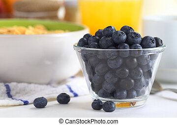 Fresh blueberries in glass bowl with a bowl of cereal, orange juice and cup in the back (Selective Focus, Focus on the blueberries in the front)