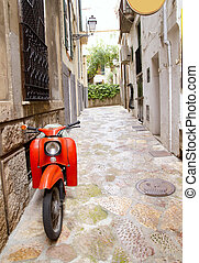 Mediterranean street with old retro red scooter in Mallorca...