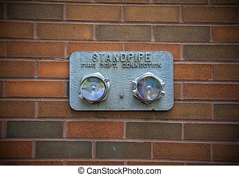 Standpipe - Silver-color standpipe is located on red bricks...